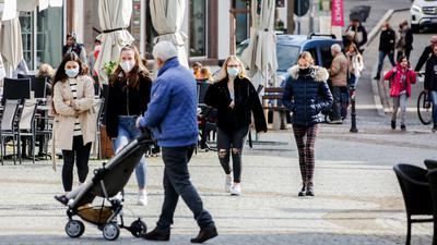 Passanten mit Masken in der Brettener Fußgängerzone.