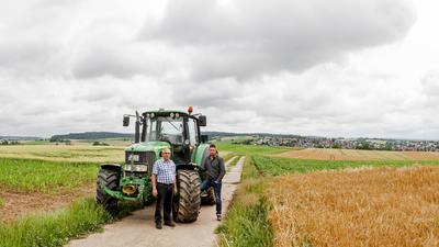 Zwei Männer mit Traktor auf Acker