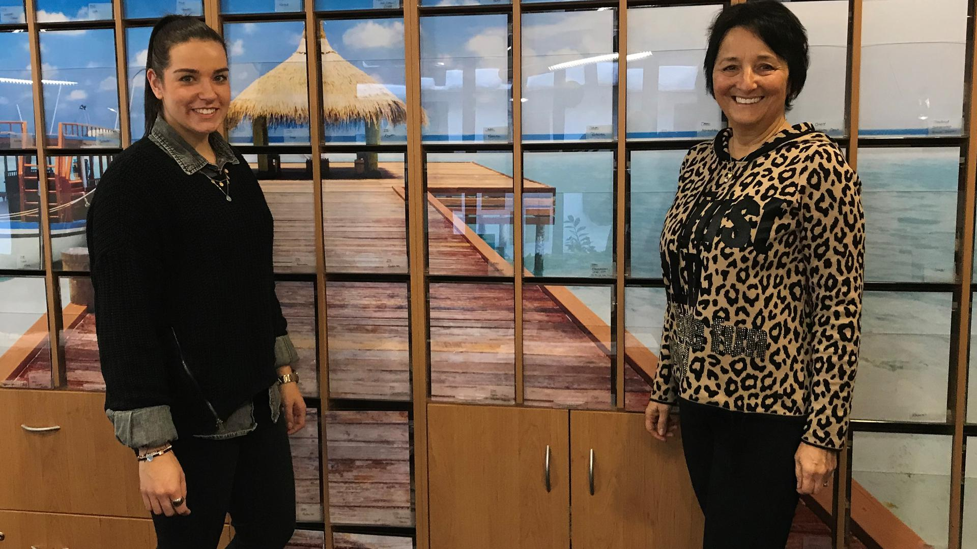 Zwei Frauen vor einem Urlaubsmotiv in einem Reisebüro.