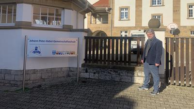 SPD-Kandidat Stephan Walter steht neben dem Schild der Brettener Hebel-Schule.