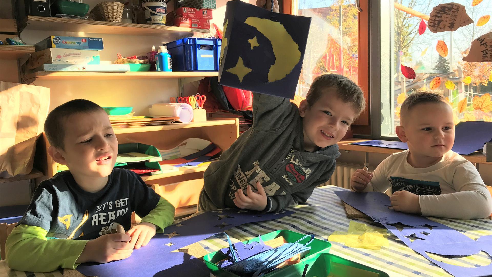Drei Jungen basteln Laternen an einem Tisch im Kindergarten.