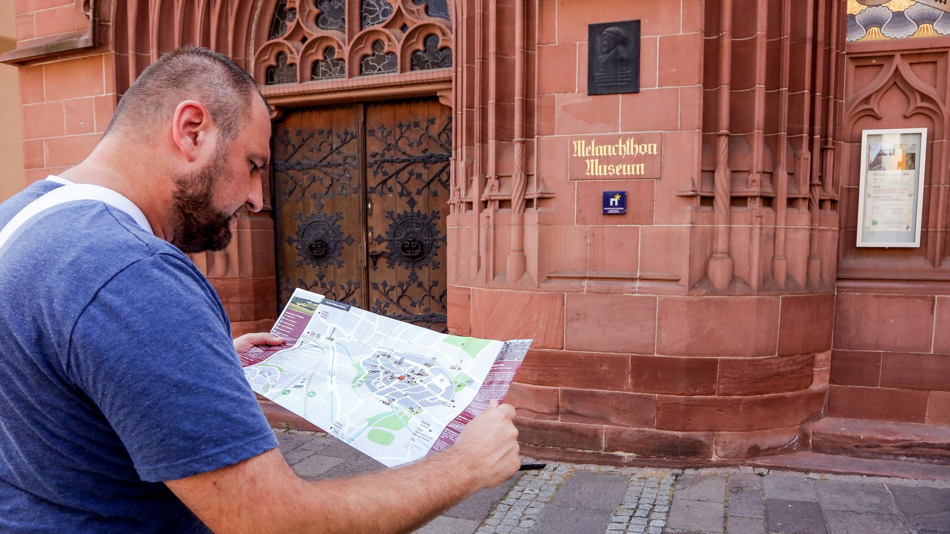 BNN-Redakteur Christof Bindschädel steht mit Stadtplan vor dem Melanchthon-Museum . Foto: Tom Rebel