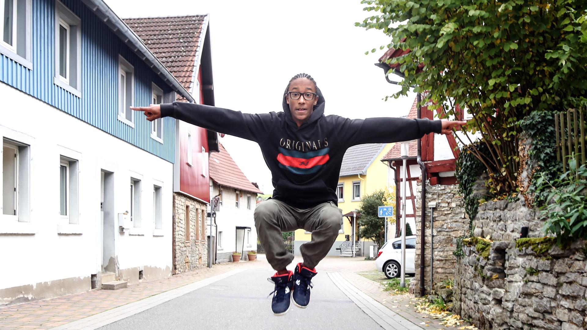 Streetdancer Moses Schäfer in der Luft mit ausgestreckten Armen.