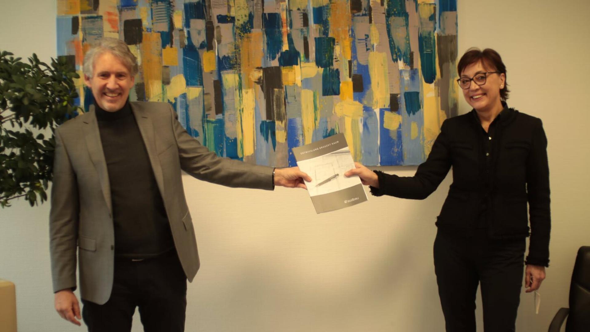Frau und Mann reichen sich Papierblatt.