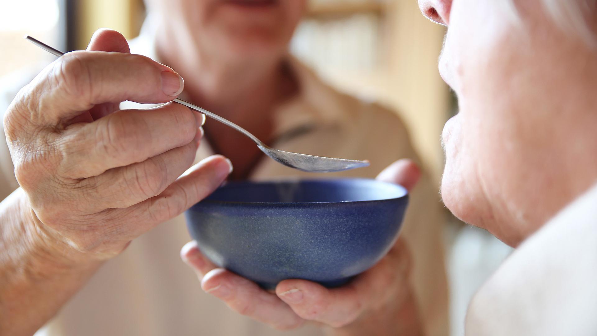 Eine Helferin reicht einer Seniorin das Essen.