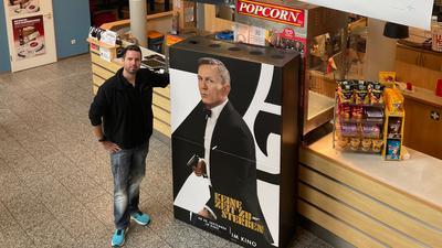 Theaterleiter Lars Skoda steht mit einem Bond-Aufsteller im Foyer des Kinos in Bretten.