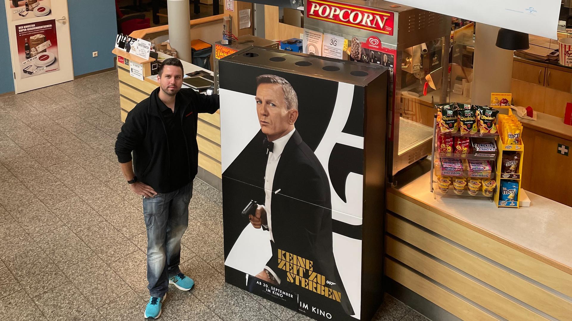Ein Mann mit Werbeplakat für Kinofilm.