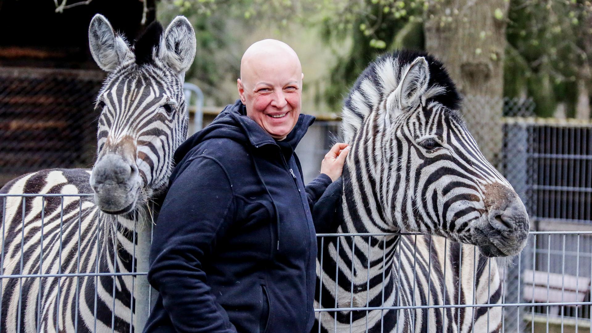 Tierpark-Chefin Annika Willig streichelt zwei Zebras.