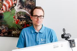 Ein junger Arzt am PC vor der Kamera am Bildschirm.