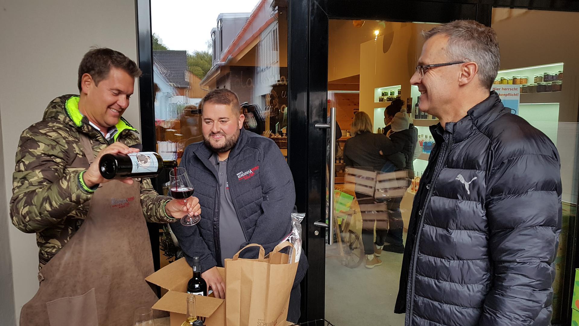 """Mallorca-Partysänger Peter Wackel (links) schenkt zur Eröffnung von """"Biber's ScheunenMarkt"""" in Großvillars gemeinsam mit Steffen Amann (Mitte) ein Gläschen für Thomas Antritter (rechts) ein."""