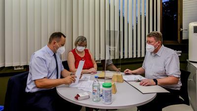 Wahlleiter Simon Bolg (links) und Diana Kern (Mitte) prüfen die Wahlergebnisse aus Dürrenbüchig von Frank Kremser (rechts).