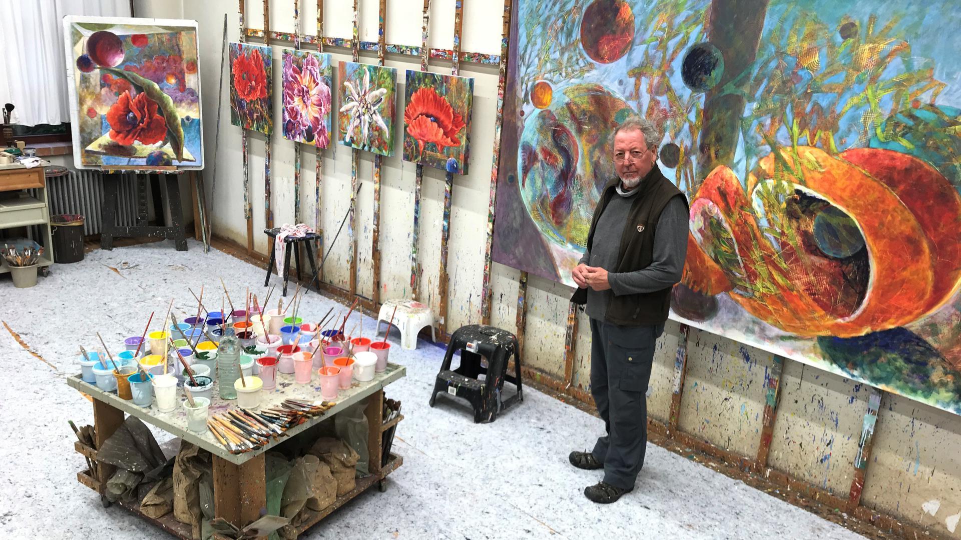 Ein Mann steht vor einem großformatigen Kunstwerk, daneben hängen viele kleiner Bilder, die vorrangig Blüten zeigen.