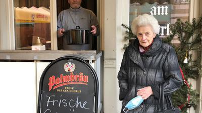 Vor dem geöffneten Fenster eines Kiosks steht eine Seniorin. Im Fenster lächelt ein Mann. Er hält einen Topf in seinen Händen.