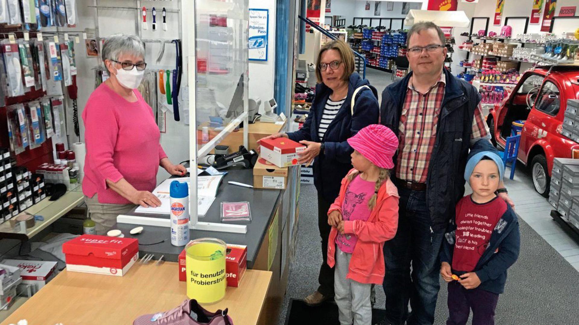 Einkaufserlebnis statt Online-Shopping: Familie Wolf aus Diedelsheim nutzt gleich den ersten Tag der Geschäftsöffnung, um bei Schuhmode Noll in der Brettener Fußgängerzone Sandalen für die Kinder zu kaufen.