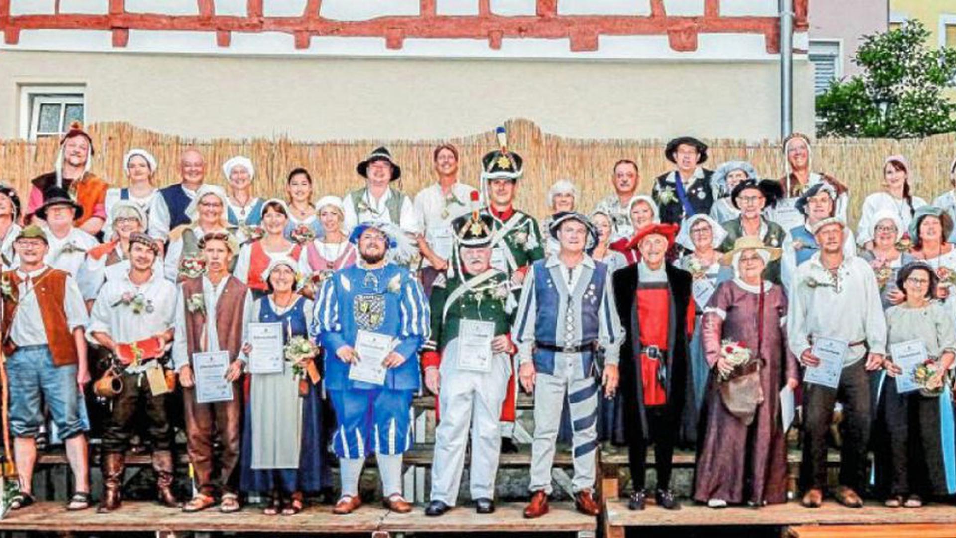 Verdiente Aktive wurden beim Empfang der Vereinigung Alt-Brettheim auf dem Kirchplatz von Stadtvogt Peter Dick (vorn Mitte mit rotschwarzem Gewand) und Schultheiß Martin Wolff (daneben) geehrt.