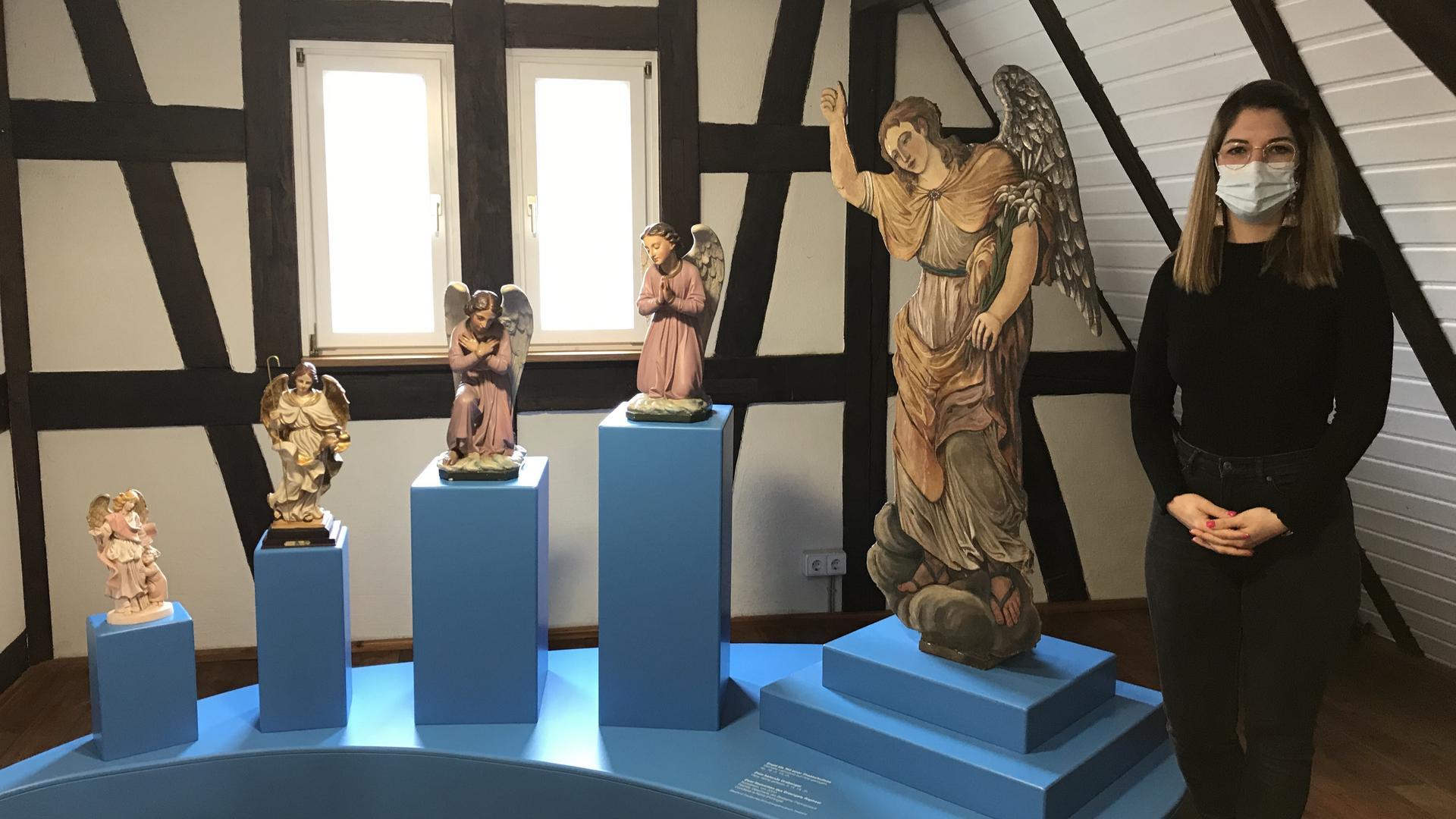 Linda Obhof steht im Schutzengelmuseum neben Engelsfiguren