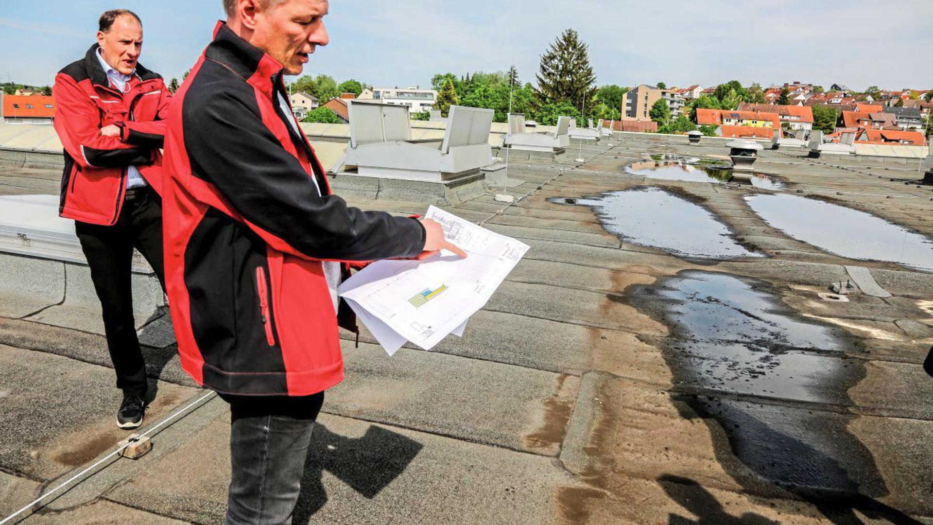 Jürgen Schaub und Martin Hartmann, Vertreter der Firma BSH/Neff, stehen auf dem Dach des Presswerks an dem Standort der künftigen Lüftungsanlage. Im Hintergrund ist das Wohngebiet zu sehen, in dem die Anwohner weiteren Lärm fürchten.