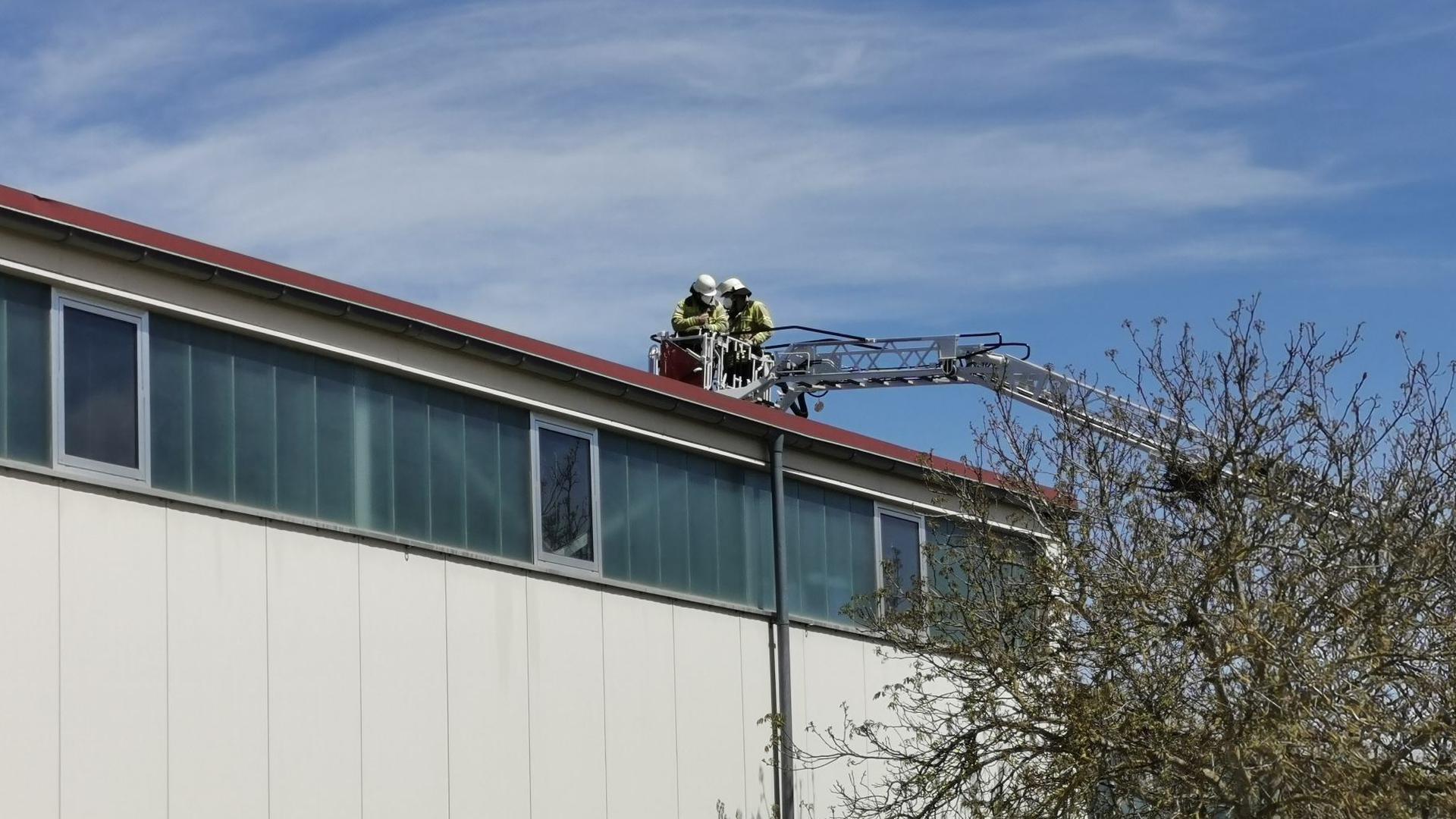 Zwei Feuerwehrleute werden mithilfe einer Drehleiter auf das Dach einer Lagerhalle gehoben.