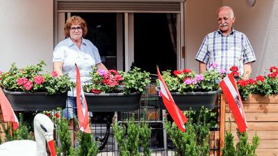 Mann und Frau hinter Gartenzaun