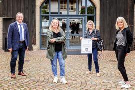 Mann und drei Frauen vor historischem Gebäude