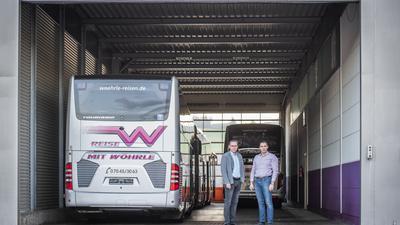 Zwei Männer stehen neben einem Bus