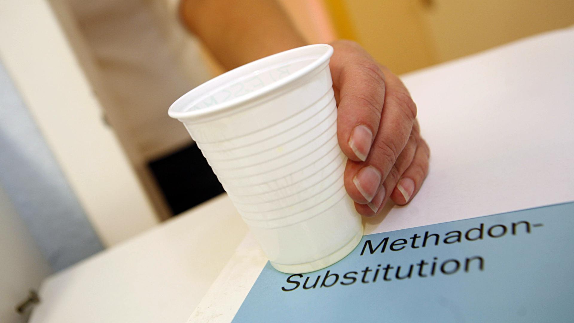 Eine Hand greift nach einem Becher mit 100 Milligramm Methadon.