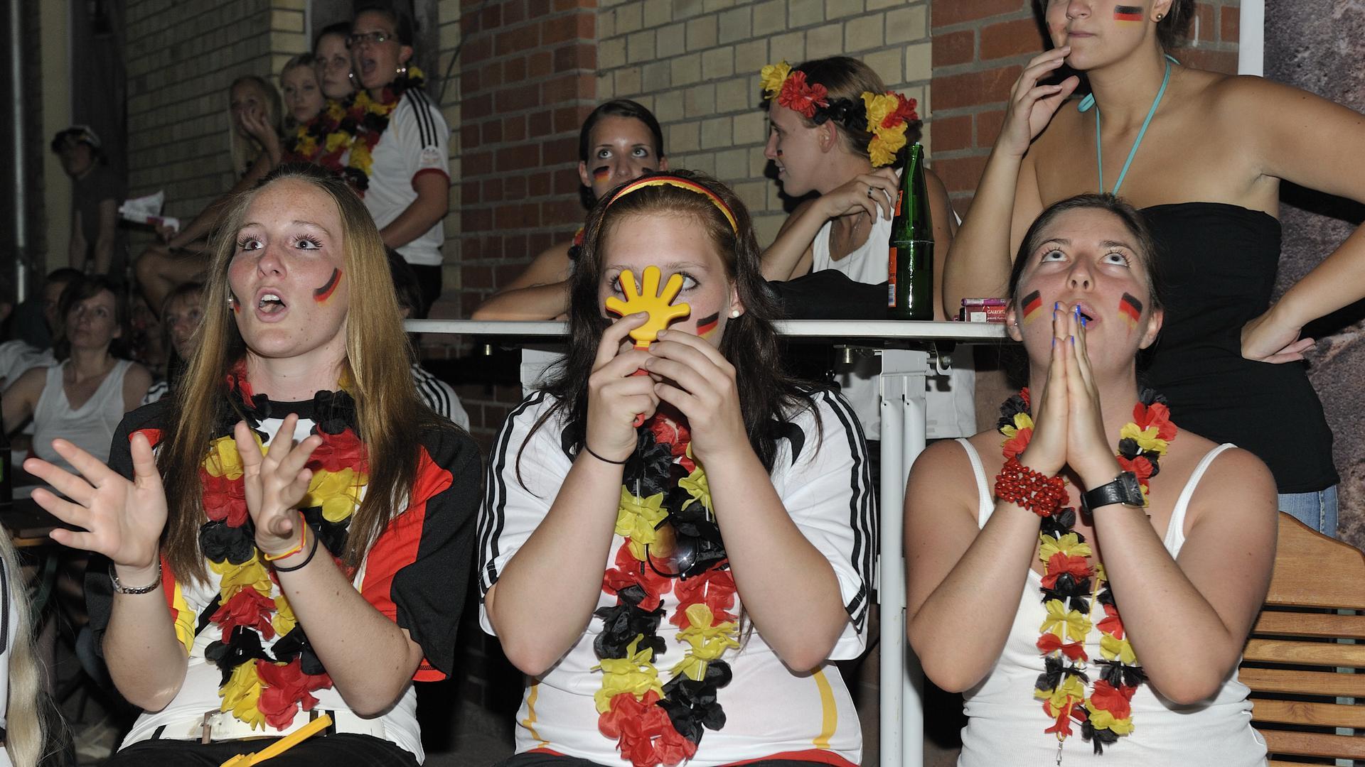 Frauen mit Fußball-Fanutensilien und deutschen Farben