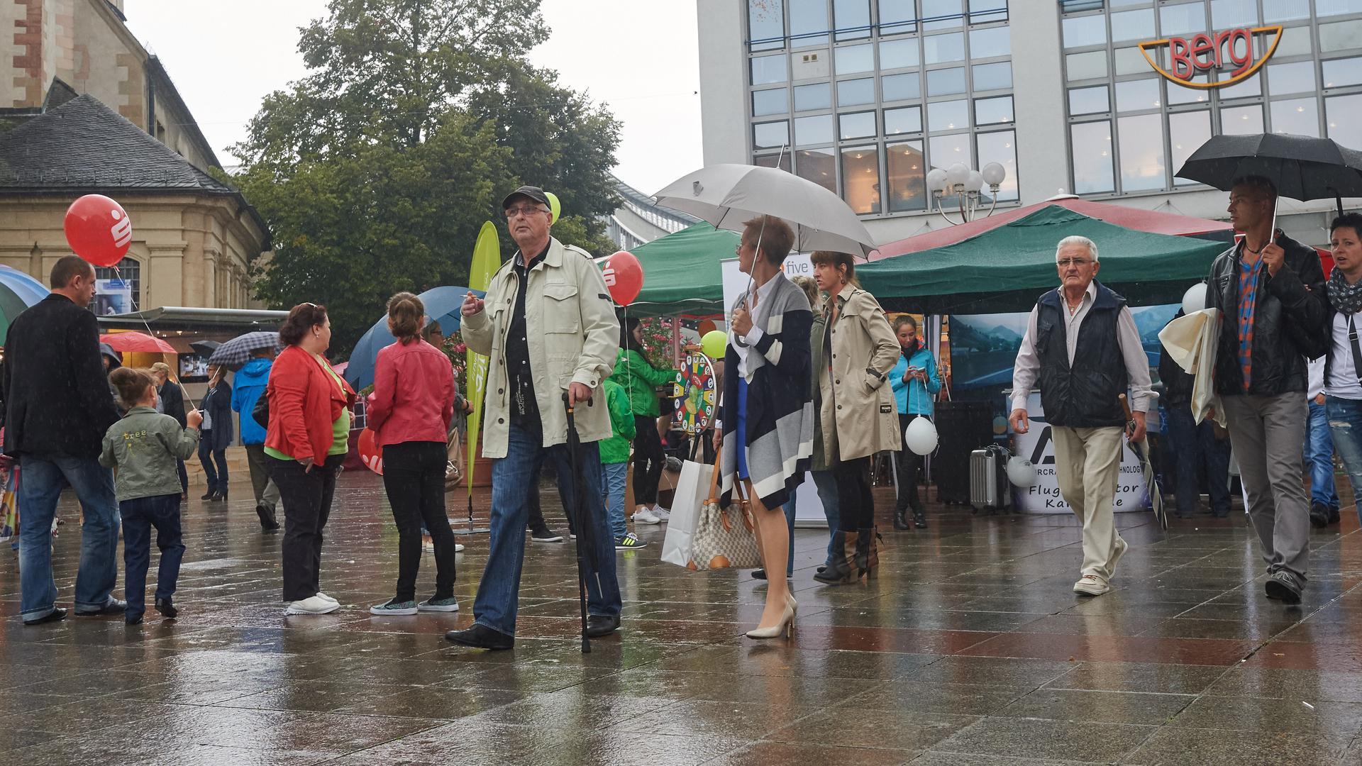Leute im Regen auf Platz.
