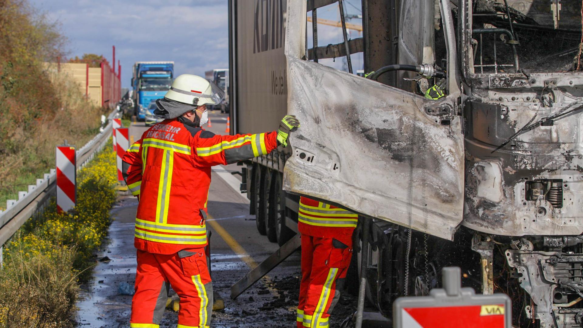Zwei Einsatzkräfte inspizieren das verbrannte Fahrerhaus des Lastwagens.