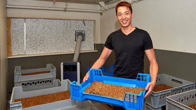 Gia Tien Ngo steht im Zuchtraum seiner Insektenfarm und hält eie Kiste mit Mehlwürmen hoch