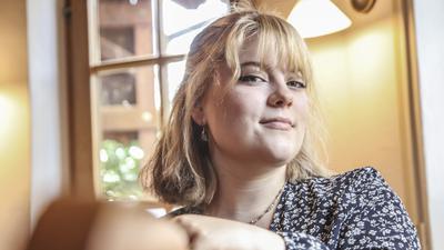 Junge Frau schaut in die Kamera, während sie am Esstisch sitzt.