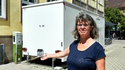 Monika Bucher vor dem Toilettenwagen  auf der Stellfläche  der Ladestation am Rathaus.