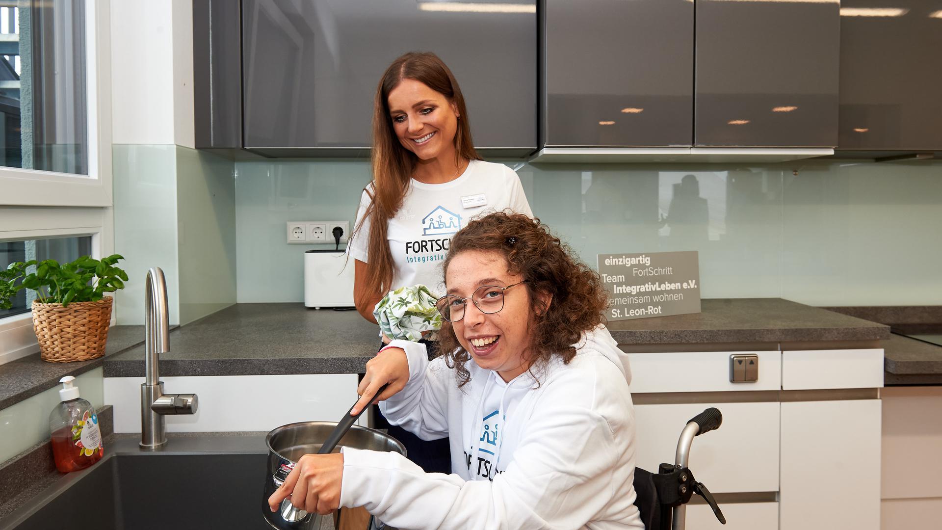 Zwei Frauen in Küche, eine im Rollstuhl.