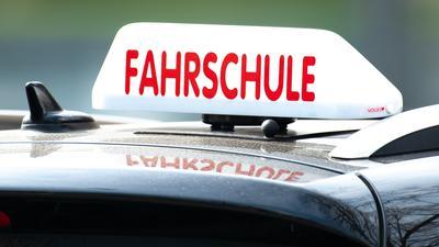 Ein Schild mit der Aufschrift «Fahrschule» ist auf einem Fahrschulauto befestigt.
