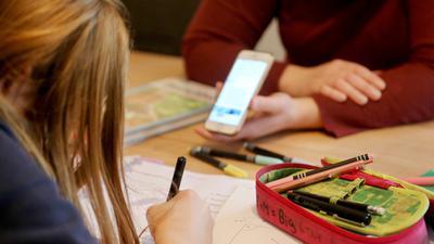 Eine alleinerziehende Mutter (r) hilft ihrer zwölfjährigen Tochter beim Homeschooling