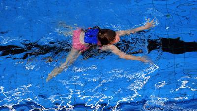 Ein Mädchen mit Schwimmhilfen im Becken einer Schwimmhalle, Symbolbild Schwimmkurs