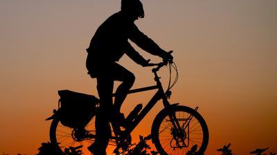 ILLUSTRATION: Ein Radfahrer steht am 30.07.2013 im Sonnenuntergang mit seinem Trekkingrad am Rande eines Feldes nahe Sieversdorf (Brandenburg). Immer mehr Touristen entdecken Brandenburg als Fahrradland. Rund drei Millionen Radler wurden laut Tourismus-Marketing Brandenburg GmbH (TMB) nach den jüngsten vorliegenden Angaben aus dem Jahr 2011 an den offiziellen Radzählstellen registriert. Foto: Patrick Pleul/dpa ++ +++ dpa-Bildfunk +++