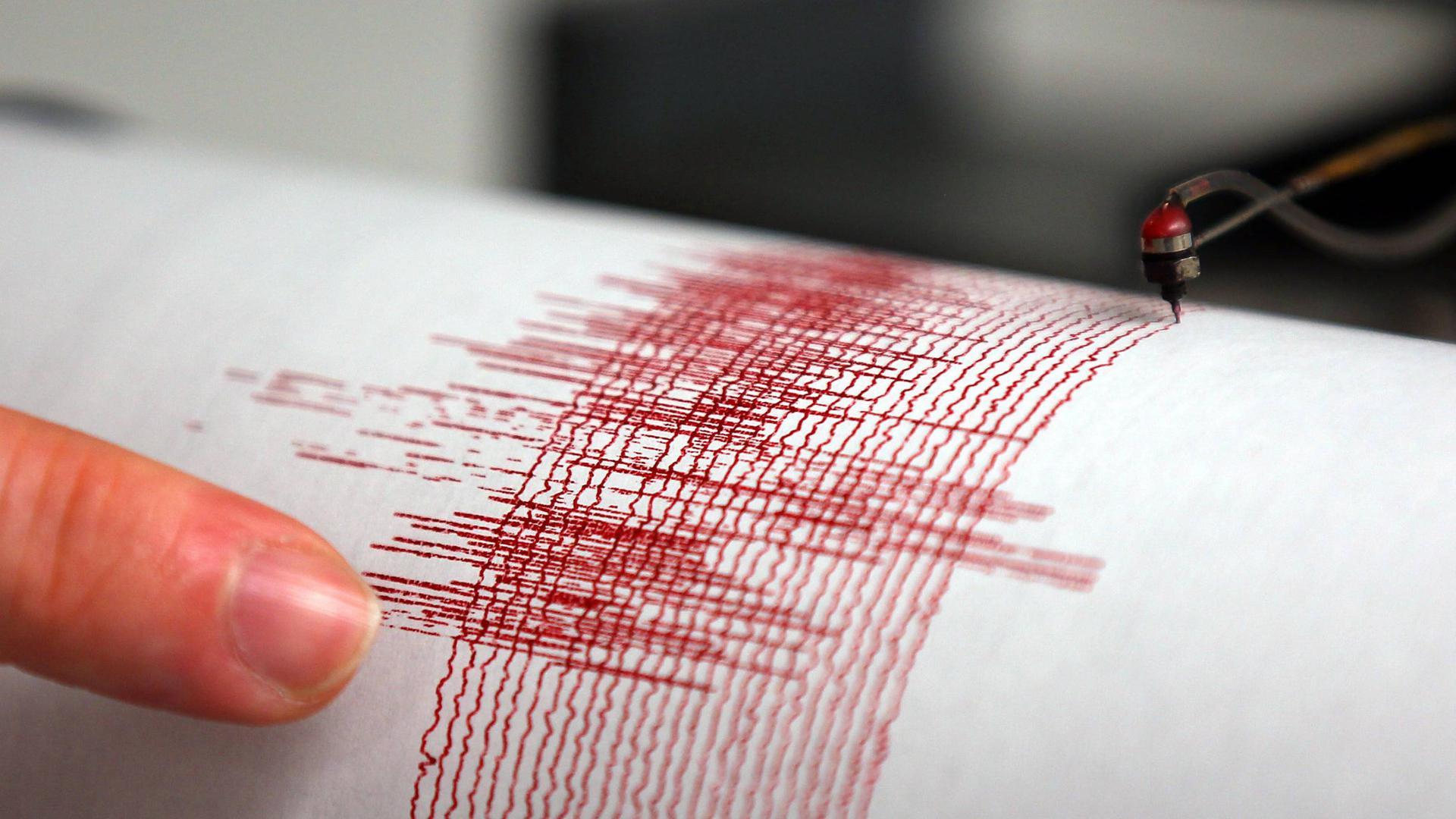 Ein Seismograph zeichnet die Stärke eines Erdbebens anhand waagrechter roter Linien auf.