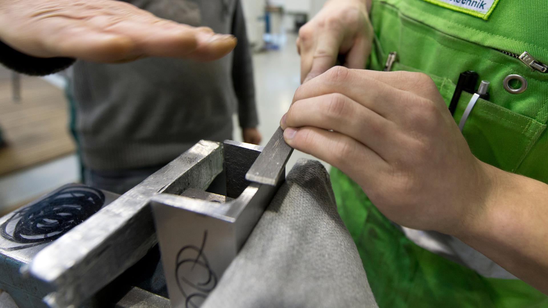 Ein Metallteil wird gefeilt.