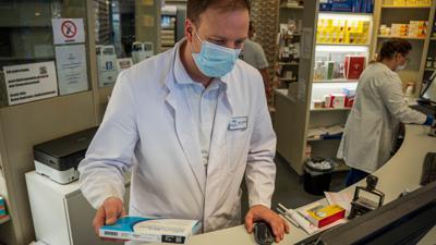 Apotheker Ernst Ciupka in der Bruchsaler Hirschapotheke mit einem Grippeimpfstoff