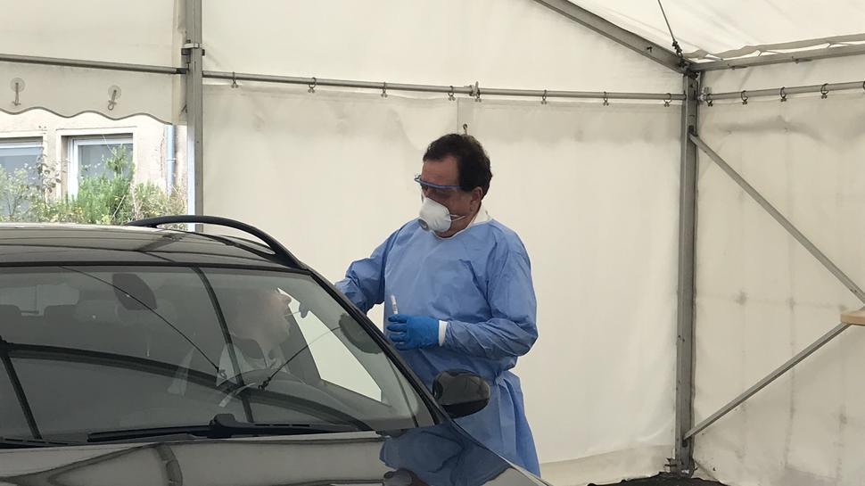 Arzt macht Abstrich, Patient im Auto