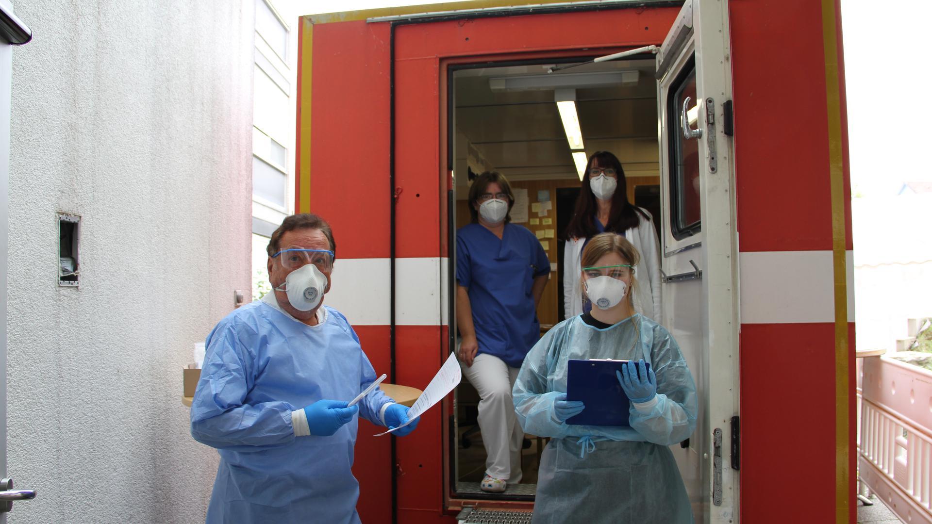 Vier Personen stehen in einer Tür. Sie tragen Schutzkleidung