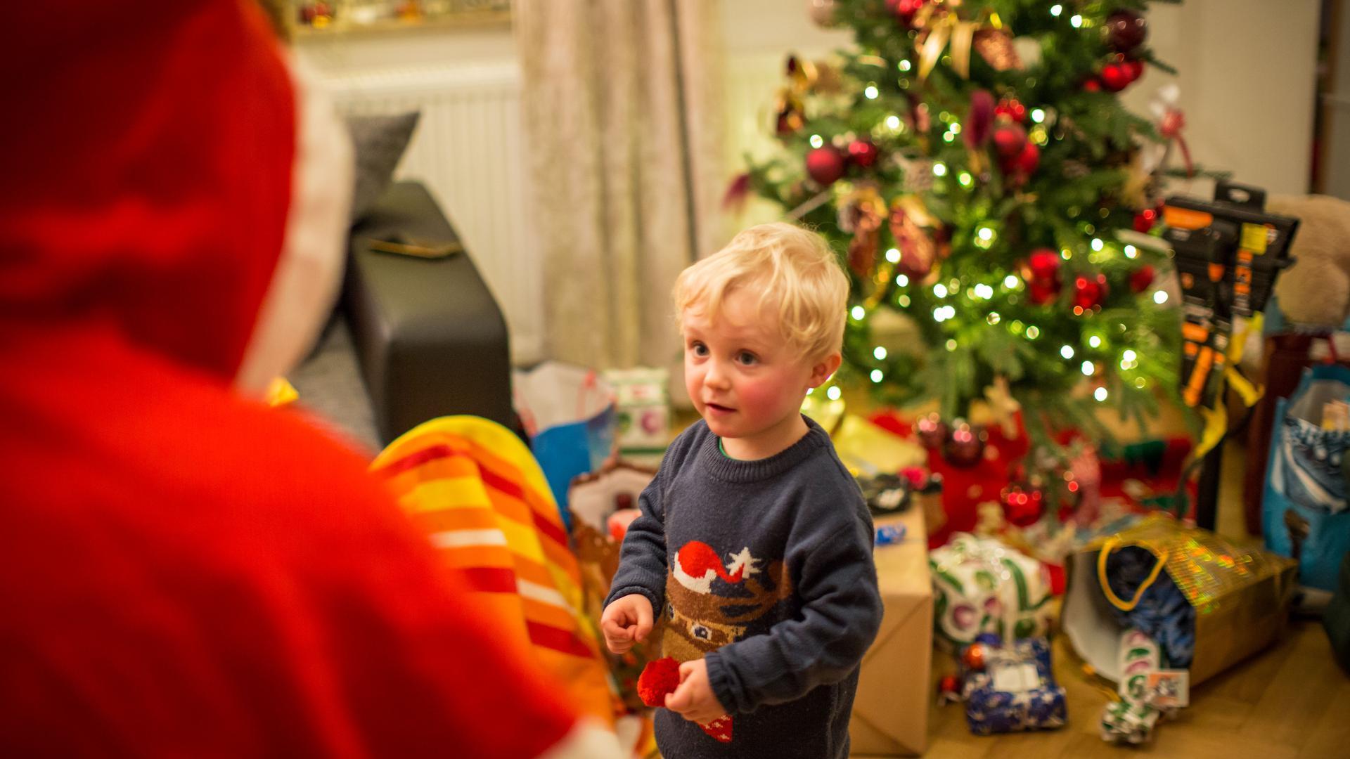 Kleiner Junge schaut den Weihnachtsmann unsicher an