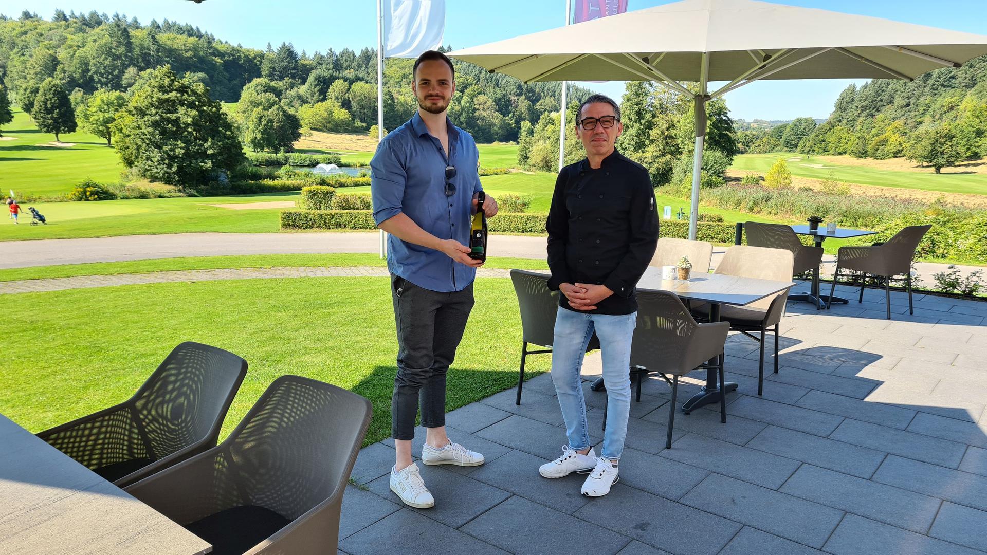"""Ein Wein mit Seltenheitswert: Philip Jacklin (links) und Küchenchef Guiseppe Peluso auf der Terrasse des Restaurants """"Albatros"""" auf dem Golfplatz in Tiefenbach. Das Resort baut einen eigenen Wein mit dem Namen Albatros aus. Von ihm gibt es nur 1.500 Flaschen pro Jahr."""