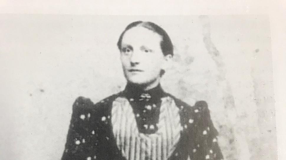 Frau mit Schutz und Korb und Milchkann.