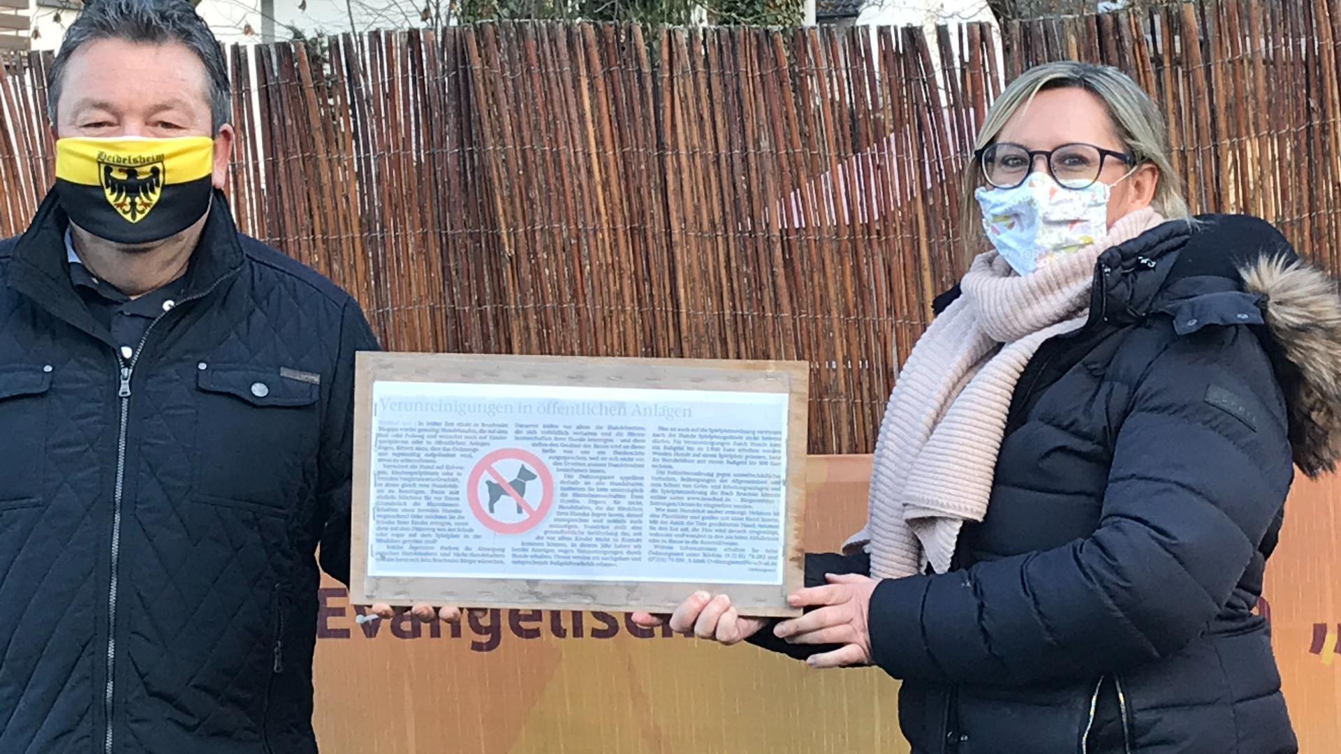 Mann und Frau mit Masken vor einem Zaun