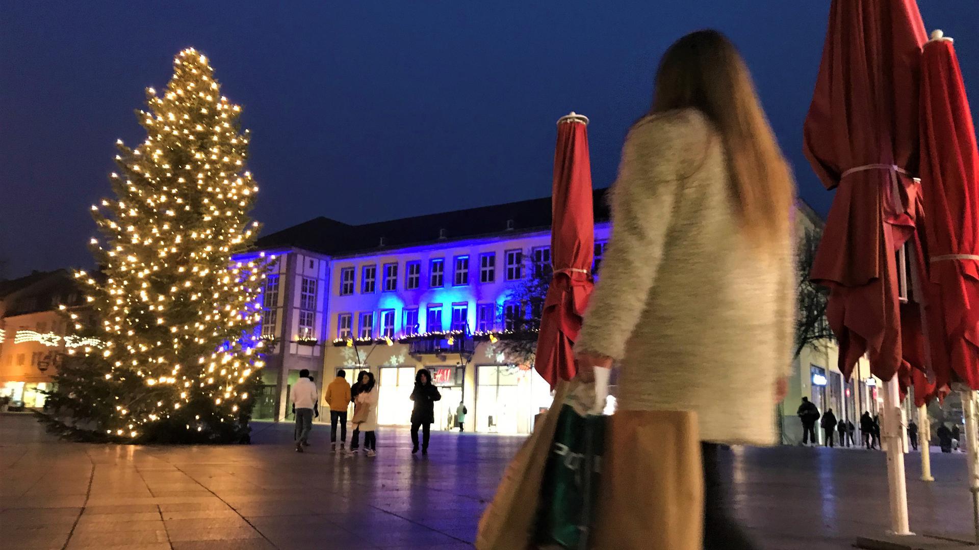 Eine Frau läuft mit mehreren Einkaufstaschen auf den Weihnachtsbaum auf dem Bruchsaler Marktplatz zu.