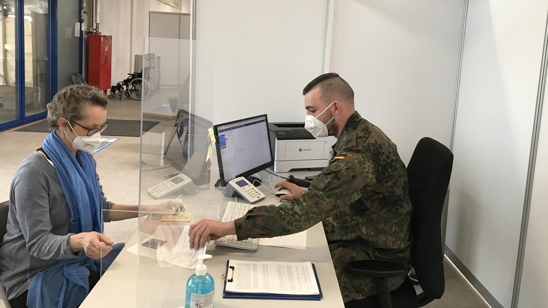 Soldat Felix Ritter gleicht die Daten der Impflinge, wie hier bei Birgit Graessel, ab.