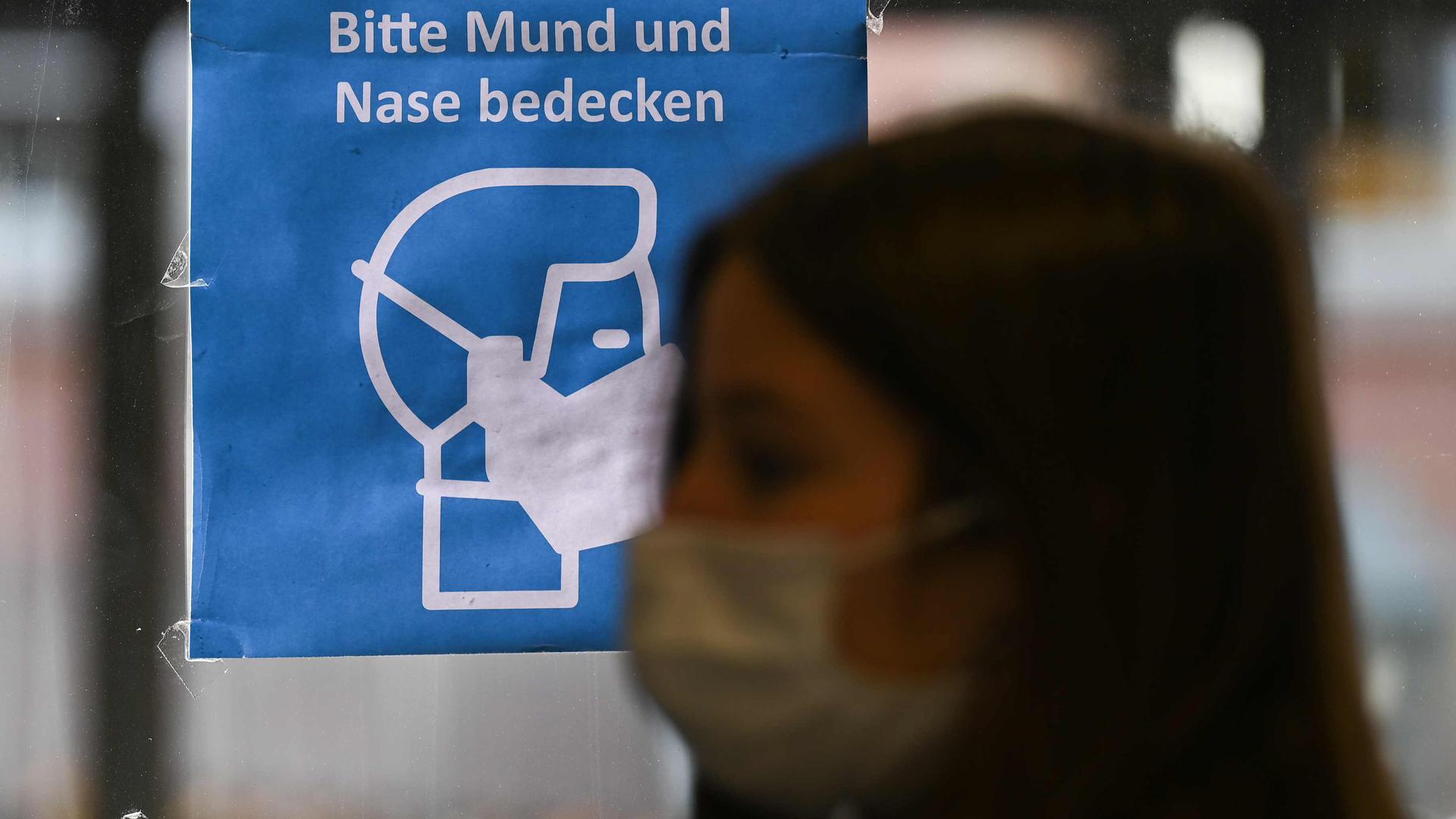 ILLUSTRATION - 07.10.2020, Rheinland-Pfalz, Mainz: Eine Frau, die einen Mund-Nasen-Schutz trägt, steht in einem Bus vor einem Plakat mit der Aufschrift «Bitte Mund und Nase bedecken». Ordnungsämter und Polizei haben in Rheinland-Pfalz die Einhaltung der coronabedingten Maskenpflicht in Geschäften, Bussen und Bahnen kontrolliert. (zu dpa «Kontrolltag: Kommunen und Polizei überprüfen Maskenpflicht») Foto: Arne Dedert/dpa +++ dpa-Bildfunk +++ | Verwendung weltweit