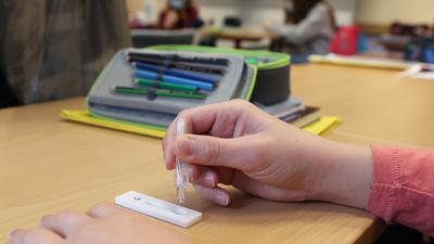 """Eine Schülerin träufelt in einem Klassenraum im """"Ökumenischen Domgymnasium"""" eine Lösung nach einem selbst durchgeführten Corona-Test auf einen SARS-CoV-2-Antigentest. (Symbolfoto)"""